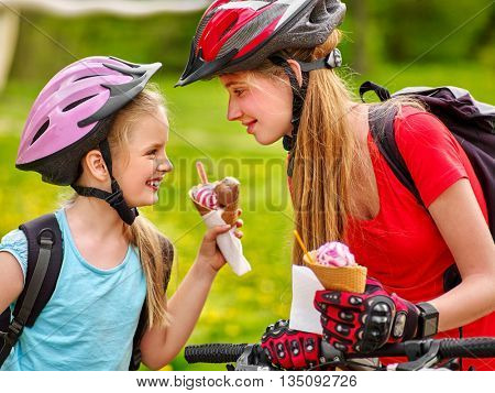 bicycle girls. Happy bicycle girls eating ice cream cone .Girls wearing bicycle helmet and gloves with rucksack rides bicycle. Children are bicycling in summer park.