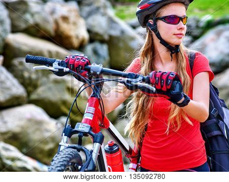 Bicycle girl. Girl rides bicycle into mountains. Girl on bicycle in mountaineering . Girl carries her bike over rocks. Bicycle travel.