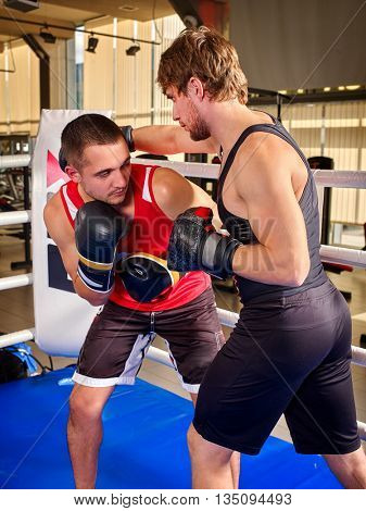 Two men boxer wearing boxing gloves are boxing . Battle took place in boxing ring.