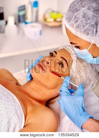 Woman middle-aged in spa salon with beautician. Beauty woman giving botox injection. Injection in nasolabial folds.