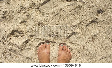 Female feet on the sand, woman's feet with pedicure on white sand beach,