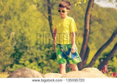 Active time on holidays concept. Young little boy walking running outdoor. Kid child spending time on fresh summer air.