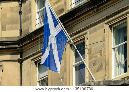 The Scottish Saltire flag on a flagpole outside a sandstone building in Edinburgh Scotland.