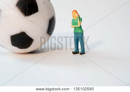 Little Person Thinking about Sports next to a Ball