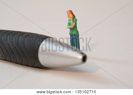 Little Person Standing Next to a Pen Thinking