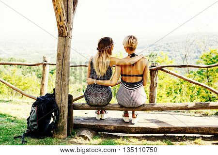 Two best friends take a break on a mountain bench