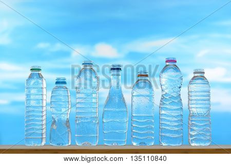 Fresh and clean drinking water in assortment of uncapped bottles with water droplet on sky background