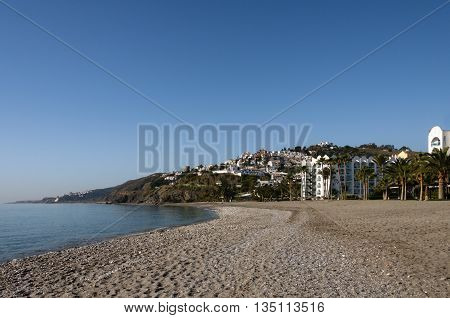 The beautiful and empty beach of Nerja at the Costa del Sol in Spain with the city itself in the background on a sunny day with blue sky and no clouds.
