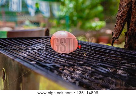 Balloon Filled With Water Placed On A Hot Grill
