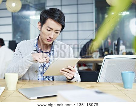 young asian business executive sitting at desk in office working using tablet computer.
