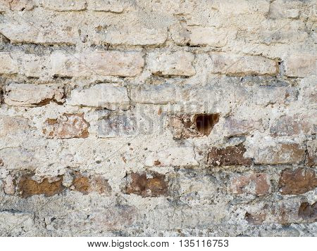 White red old grunge brick painted wall with damaged plaster texture background