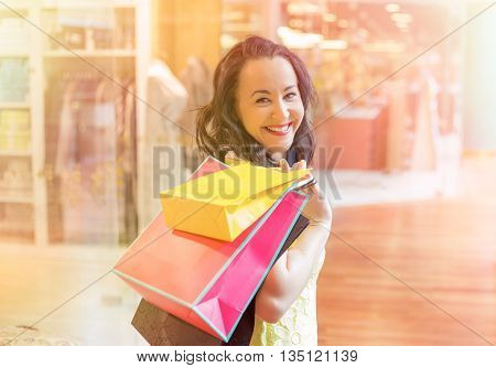 Portrait of happy woman shopping with bags over her shoulder