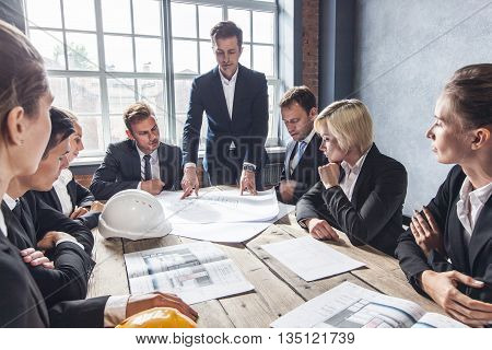 Business people group on meeting with construction engineer architect looking building blueprint