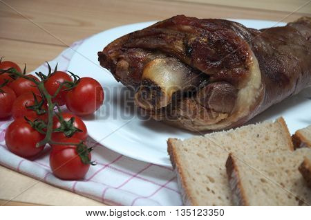 Close view photo of tasty ham hock or pork knuckle from a pig with knife bread and fresh cherry tomatoes on wooden desk. Smoked dried meat food.