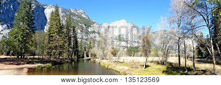 The Merced River in Yosemite Valley in Yosemite National Park in California, striking rocks of the Sierra Nevada markante Felsen der Sierra Nevada with Yosemite Falls, landscape in autumn, blue sky, panoramic,