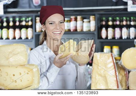 Happy Saleswoman Holding Fresh Cheese In Store