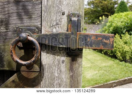 An old rusty metal garden gate latch