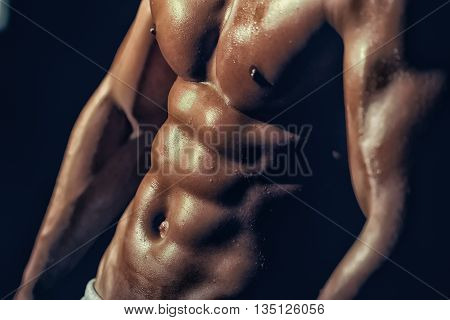 sexy muscular male torso six packs on wet body of athletic man training with bare chest and strong biceps on hands closeup poster