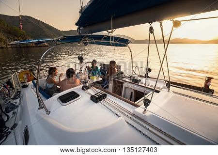 Group of young people have a dinner in anchored yacht during sunset
