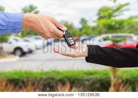 Businesswomen giving a key car to businessman at car parking.
