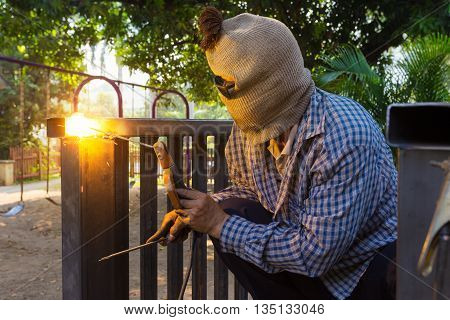 Unidentified hooded man welding steel platform bright light and sparks outdoor with blur background trees