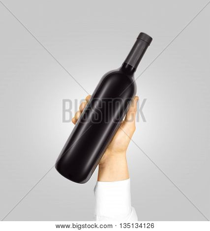 Blank black label mockup on black bottle of red wine in hand isolated. Alcohol bottle mock up presentation ready for branding design.