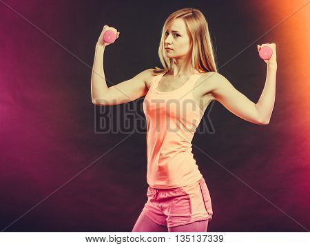 Bodybuilding. Strong fit woman exercising with dumbbells. Muscular blonde girl lifting weights studio shot on dark background