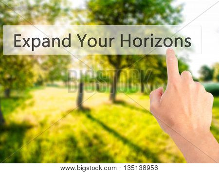 Expand Your Horizons - Hand Pressing A Button On Blurred Background Concept On Visual Screen.