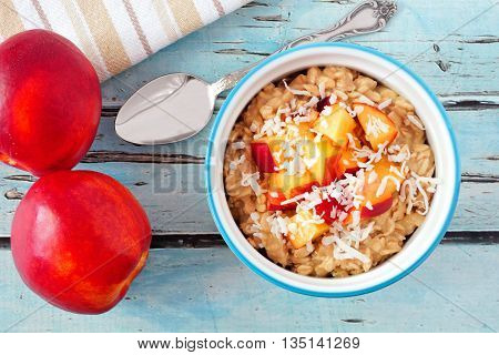 Bowl Of Overnight Breakfast Oats With Diced Peach And Coconut, Overhead Scene On Rustic Blue Wood