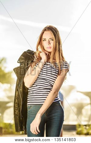 Fashion young blonde woman casual style leather jacket in hand on city street