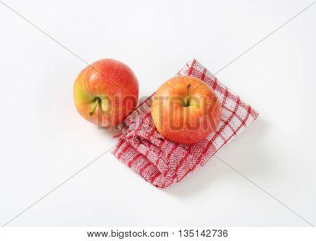 two ripe apples on checkered dishtowel