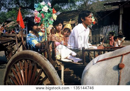 PAGAN / MYANMAR - CIRCA 1987: A man drives a decorated ox cart with his family in a Buddhist parade in Pagan during a holiday.