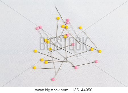 Many pins for needle work on white fabric