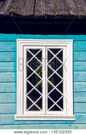 window in the old wooden blue house in the summer