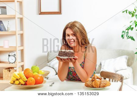 Portrait of beautiful fat woman sitting at table and holding sweety cake in front of her at home. Red haired lady smiling for camera.