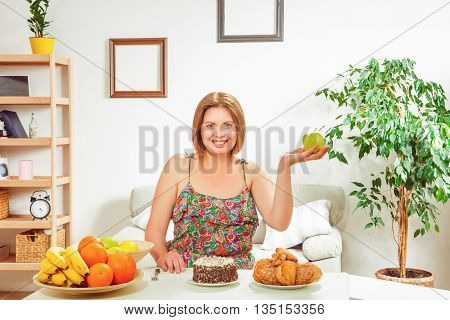 Fat woman sitting at table full of healthy and unhealthy disges at home. Happy woman looking at camera and holding apple.