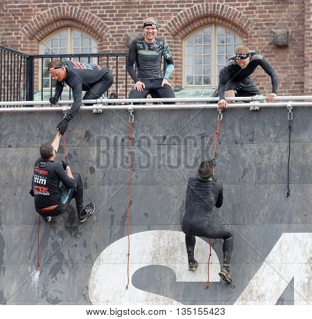 STOCKHOLM SWEDEN - MAY 14 2016: Group of men climbing the rampage obstacle hanging in rope beeing helped in the obstacle race Tough Viking Event in Sweden May 14 2016