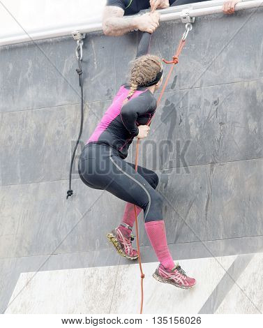STOCKHOLM SWEDEN - MAY 14 2016: Woman climbing the rampage obstacle hanging in rope in the obstacle race Tough Viking Event in Sweden May 14 2016
