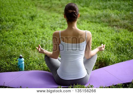 Tranquil young girl is doing yoga and relaxing in park. She is sitting in lotus positing and joying fingers. Focus on her back