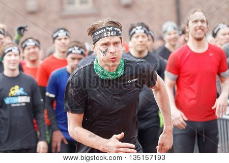STOCKHOLM SWEDEN - MAY 14 2016: Man sprinting towards the rampage obstacle competitors waiting behind in the obstacle race Tough Viking Event in Sweden May 14 2016