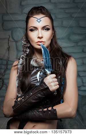 Beautiful woman with a knife she is wild and dressed in leather clothes.