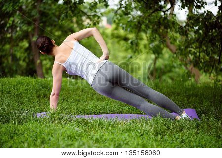 Active young girl is ding exercise on mat in the nature. Focus on her back