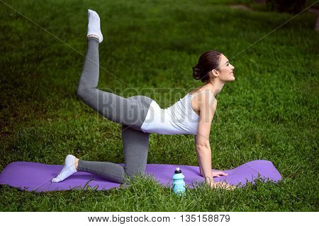 Fit young woman is doing yoga on grass. She is kneeling while stretching arm up. Lady is smiling happily
