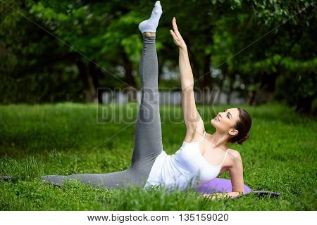 Pretty slim girl is exercising in park. She is lying on mat and smiling. Lady is stretching arm and leg up