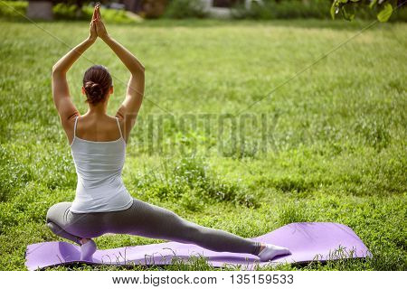 Slim healthy girl is doing exercise in the nature. She is stretching leg sideways while raising arms up. Focus on her back