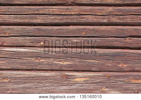 Closeup, macro of red painted logs, timber on a buildings wall. Ancient construction of putting logs together into a house.