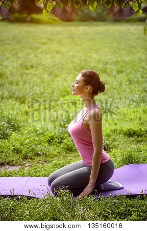 Beautiful fit girl is enjoying the nature. She is sitting and meditating. Her eyes are closed with pleasure