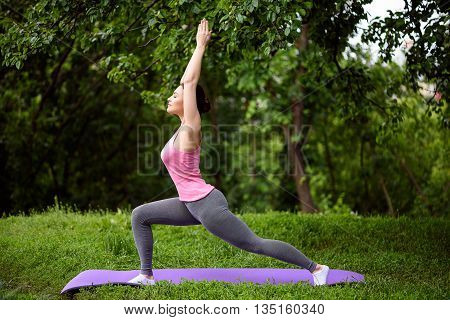 Pretty girl is exercising in park. She is standing and posing. Her eyes are closed with relaxation