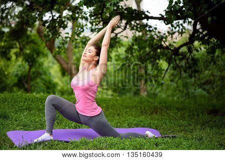 Healthy fit woman is doing yoga in the nature. She is stretching legs while raising arms up. Her eyes are closed with pleasure