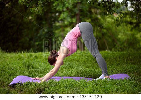 Slim young girl is stretching her body while exercising. She is standing on mat in the park